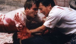 Dr. Lawrence Gordon (Elwes) and Adam Stanheight (Whannell) become brothers in blood on Saw's dingy bathroom floor.